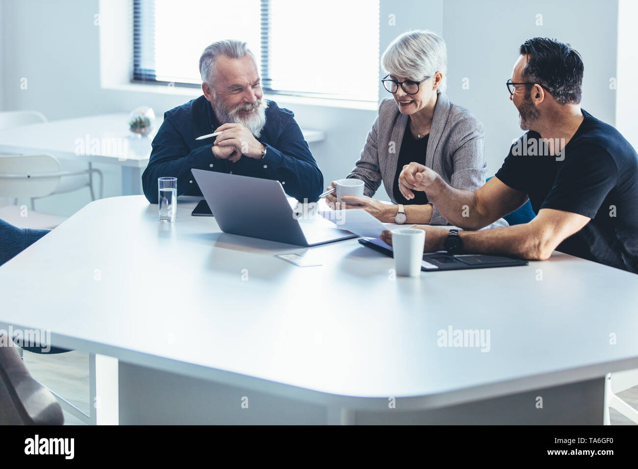 Business people discussing new business plan. Mature manager planning new strategy with colleagues in meeting. Stock Photo