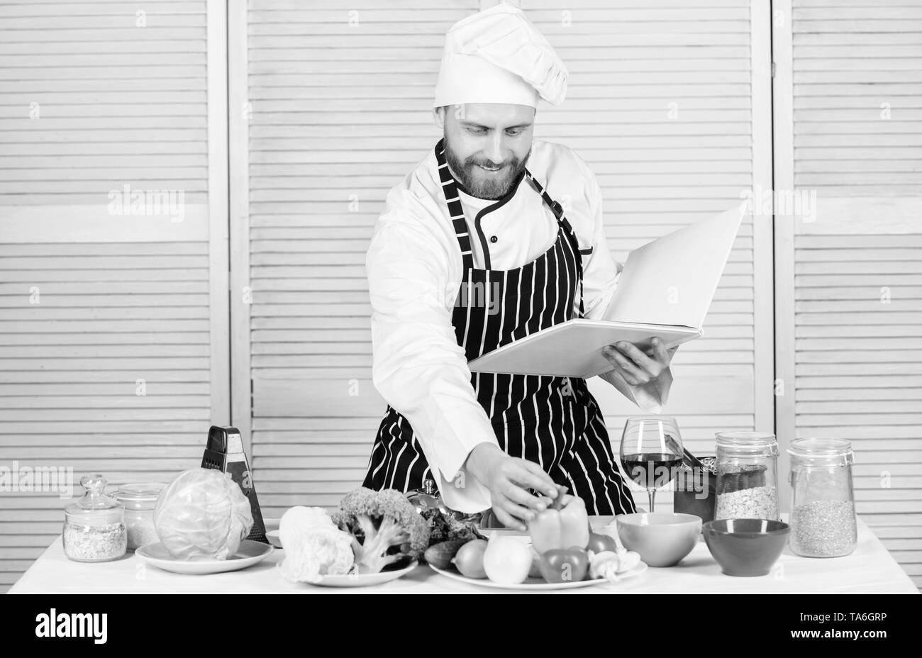 Book family recipes. Ultimate cooking guide for beginners. According to recipe. Man bearded chef cooking food. Guy read book recipes. Culinary arts concept. Man learn recipe. Improve cooking skill. - Stock Image