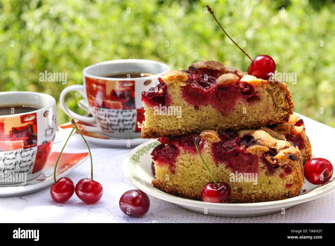Pieces of a pie with a cherry and two cups of coffee on a table outdoors, horizontal photo - Stock Image