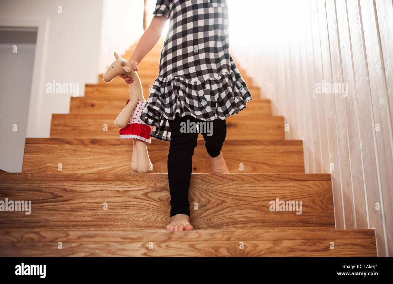 A midsection of small child with a soft toy walking down the stairs. - Stock Image