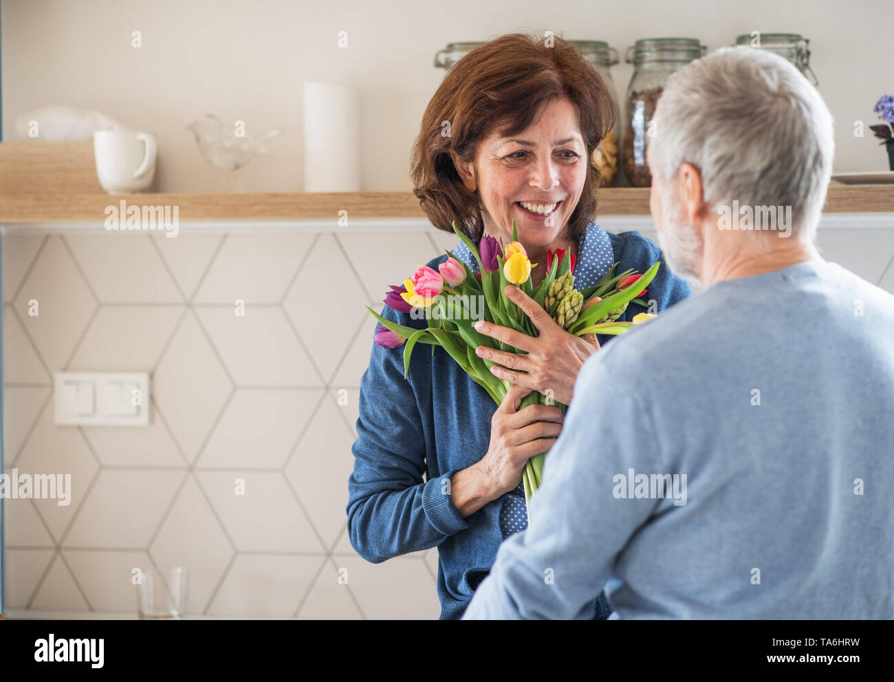 A senior couple in love indoors at home, man giving flowers to woman. - Stock Image
