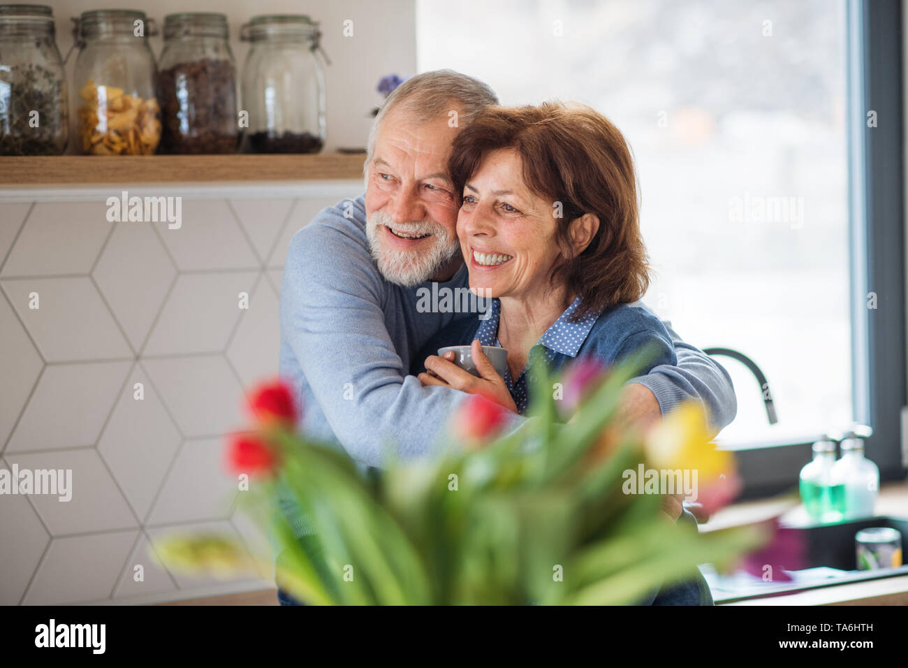 A portrait of senior couple in love indoors at home, holding coffee. - Stock Image