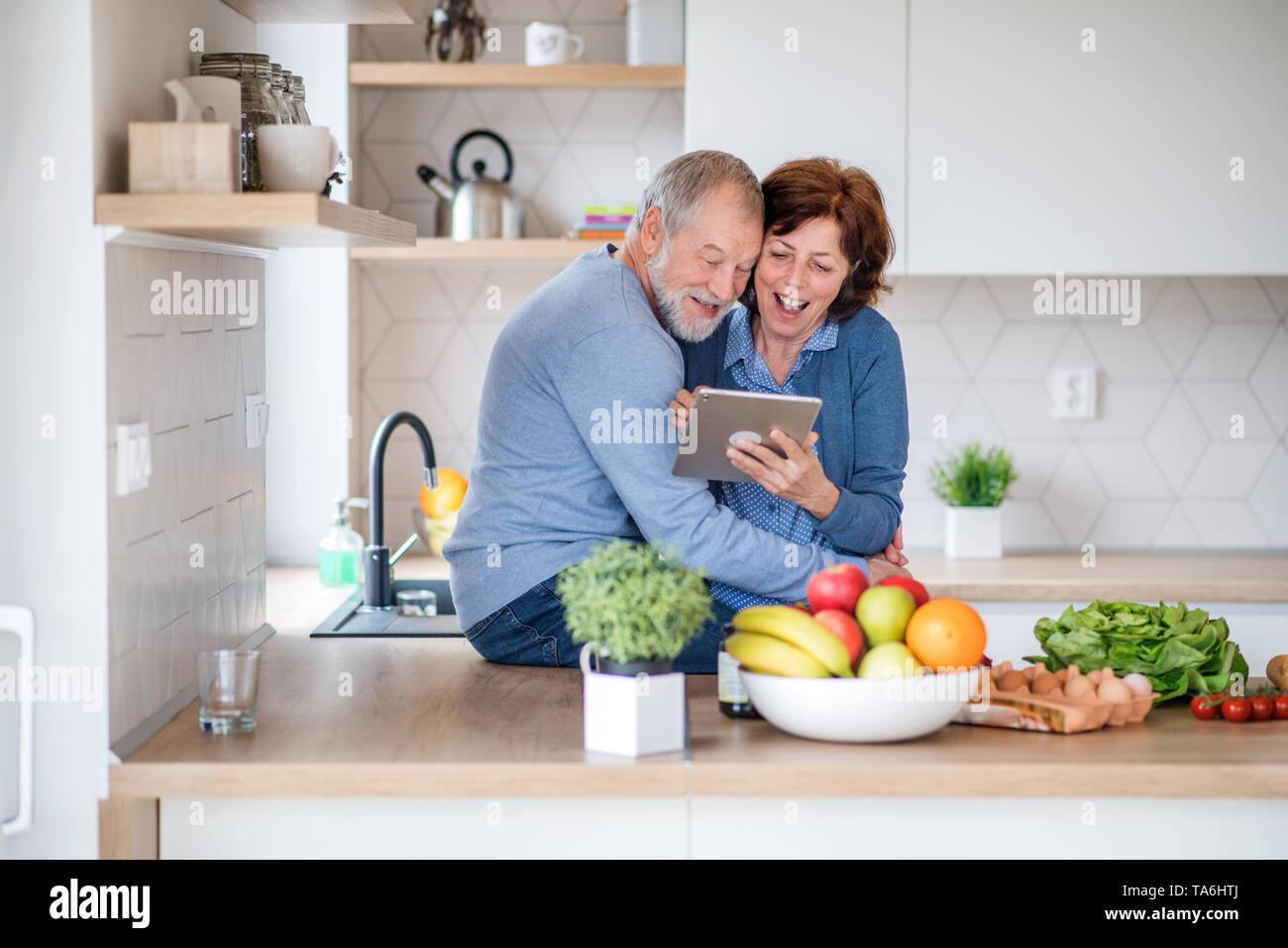 A portrait of senior couple in love indoors at home, using tablet. - Stock Image