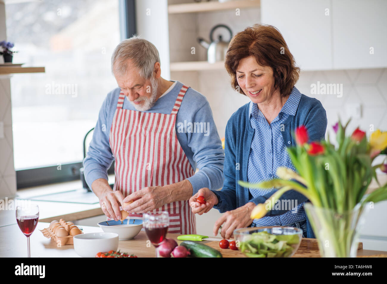 A portrait of senior couple in love indoors at home, cooking. - Stock Image