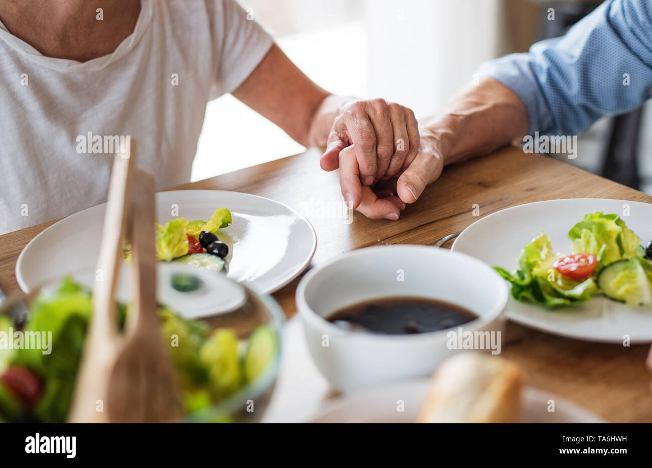 A midsection of senior couple in love indoors at home, having lunch. - Stock Image