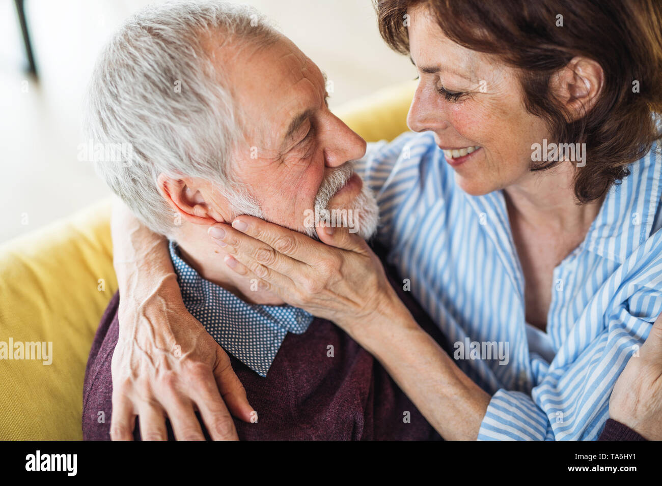 An affectionate senior couple in love sitting on sofa indoors at home. - Stock Image