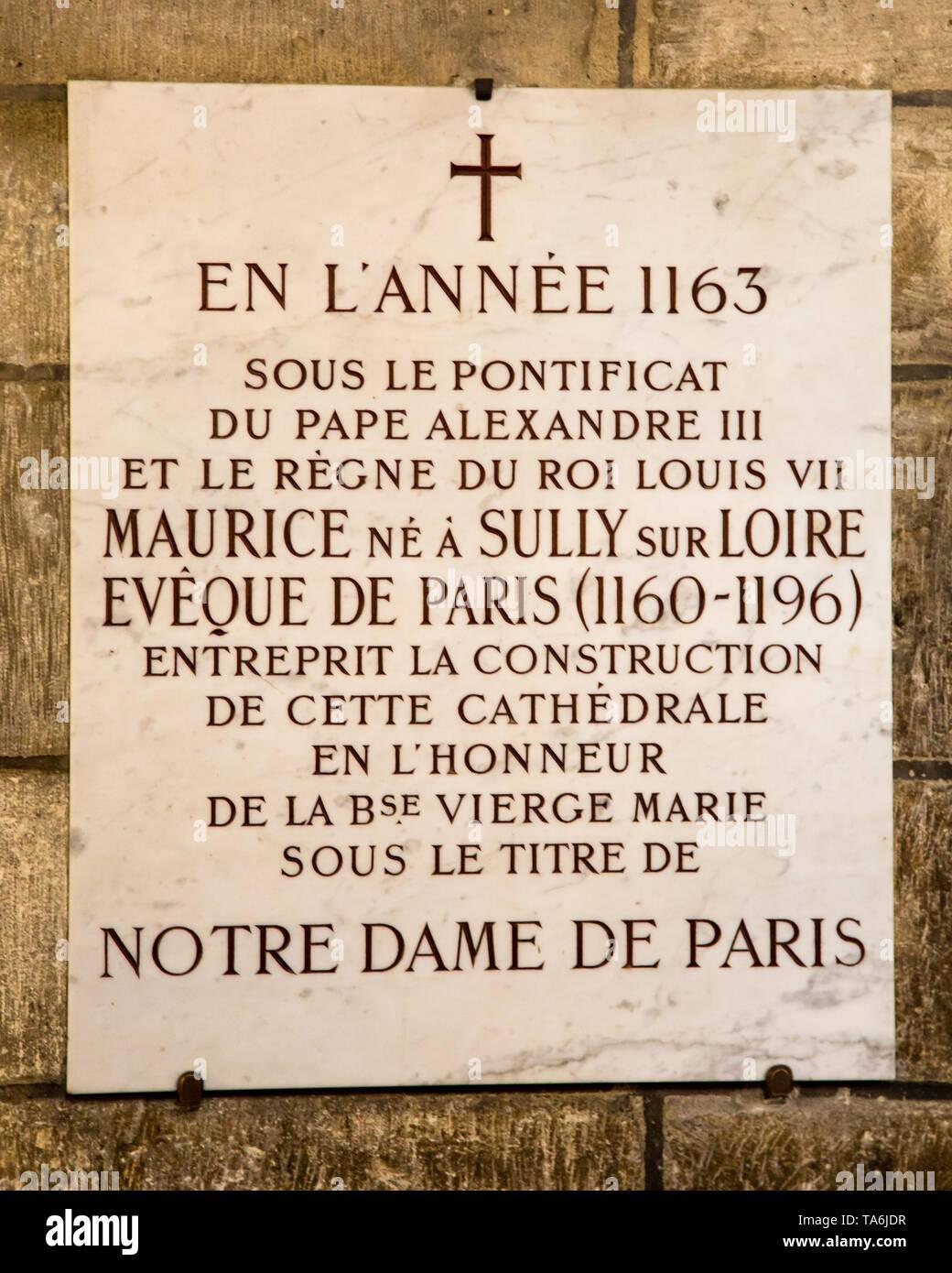 A plaque inside Notre Dame de Paris commemorating the construction, dated 1163. - Stock Image