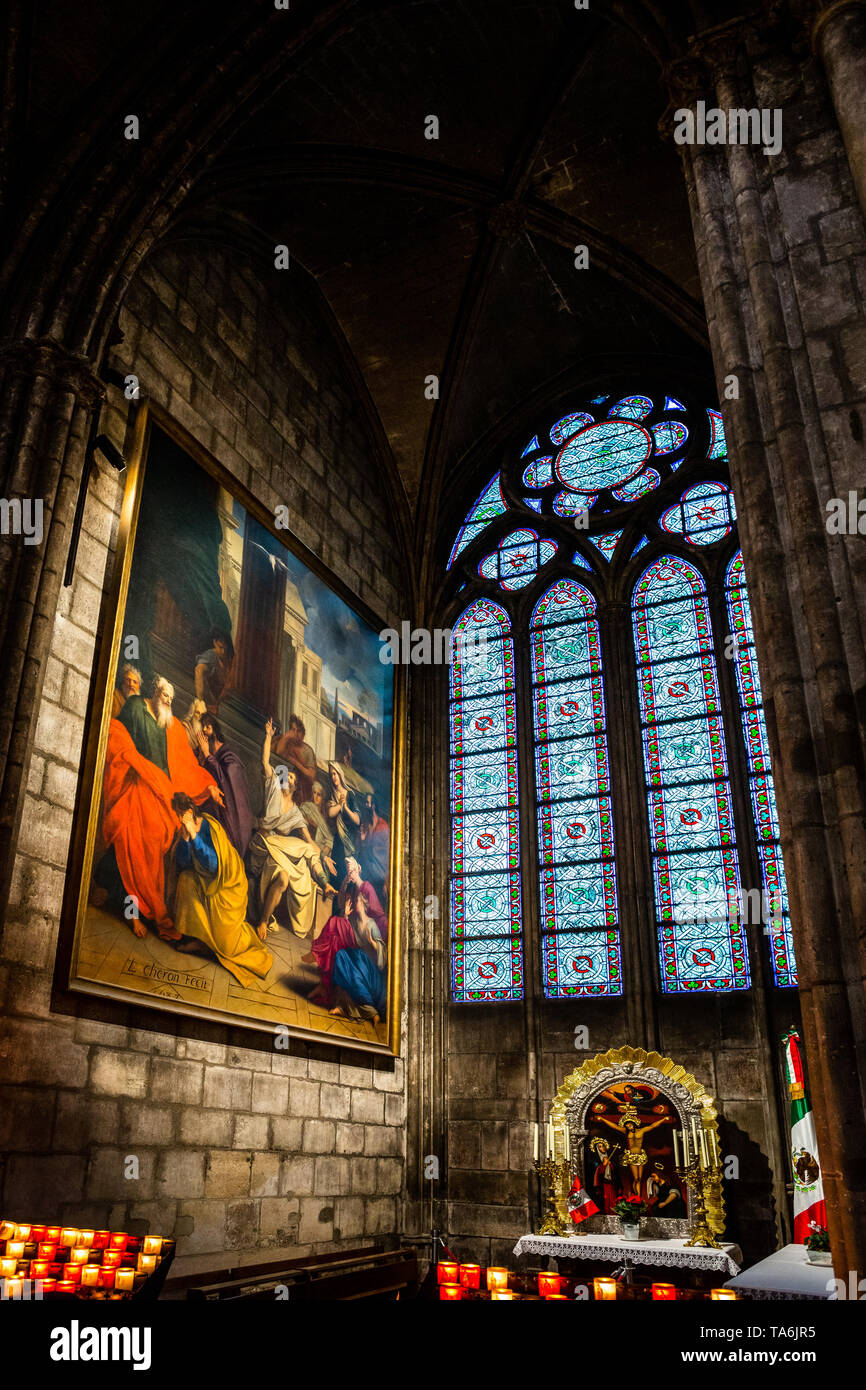 A vestibule inside Notre Dame de Paris with a painting, stained glass window and statue of christ with candles. - Stock Image