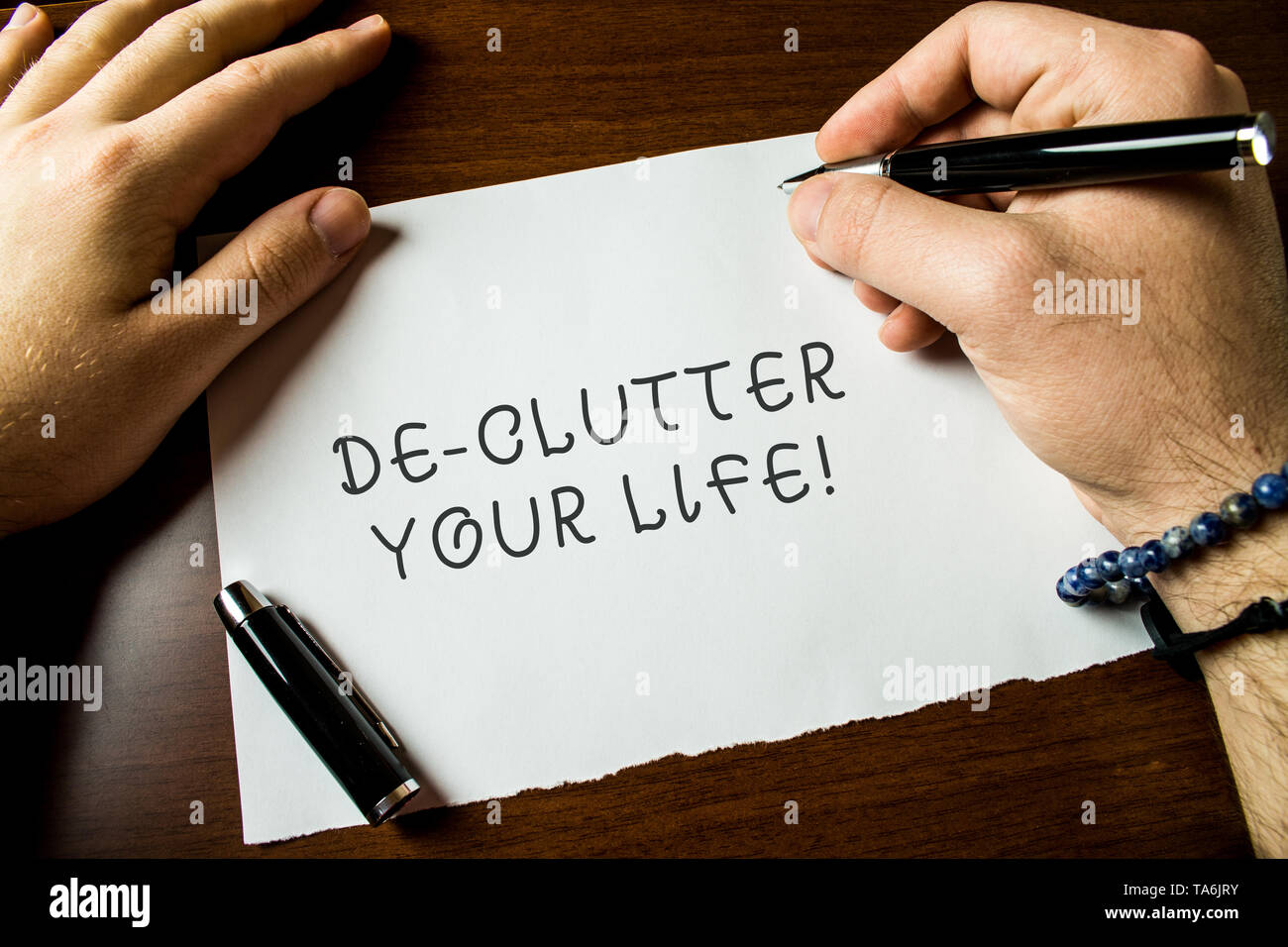 Text sign showing De Clutter Your Life. Business photo text remove unnecessary items from untidy or overcrowded places Close up view male hands writin - Stock Image