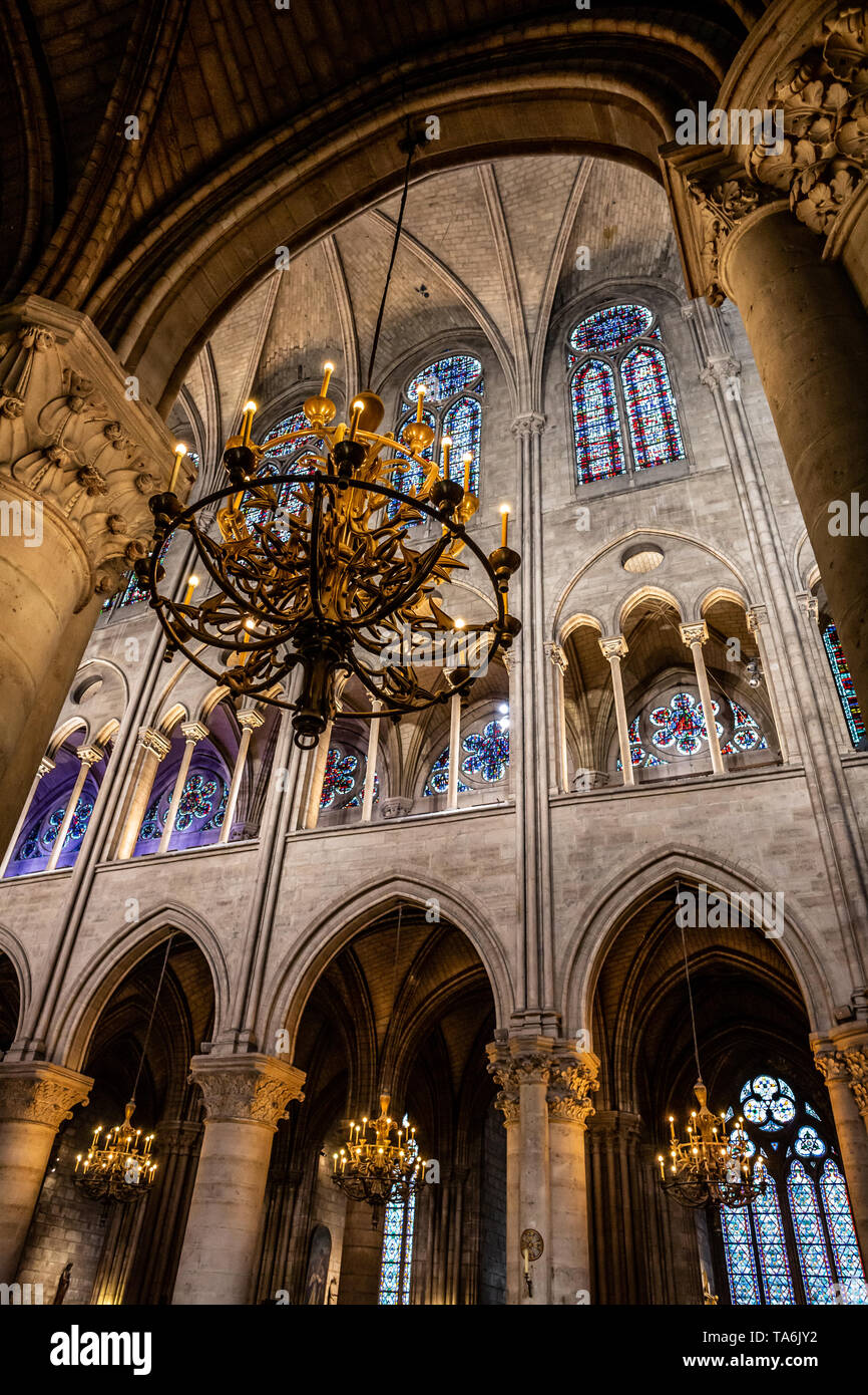 A chandelier inside Notre Dame de Paris. Several other chandeliers are in the background along with stained glass windows, columns, and ornate ceiling - Stock Image