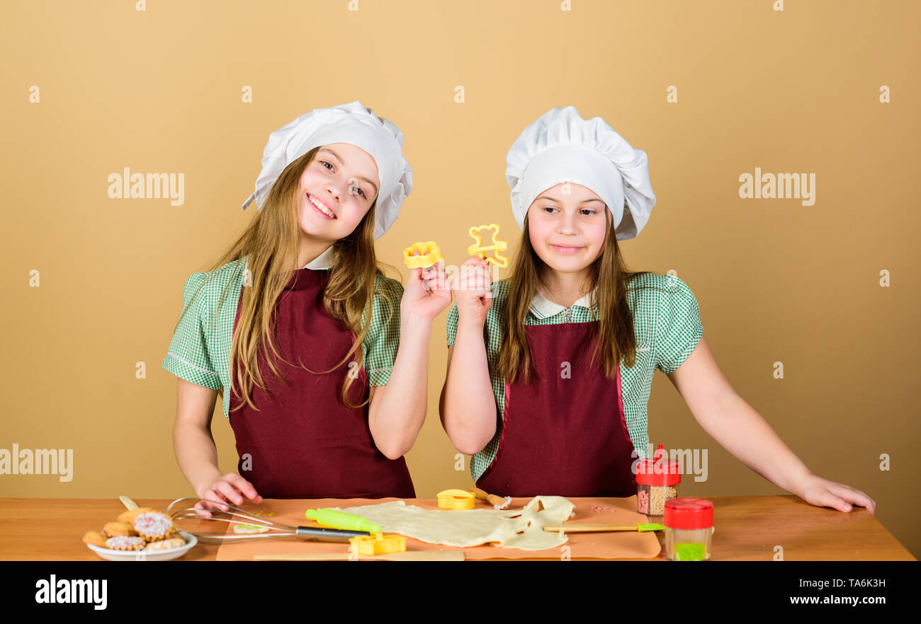 Homemade cookies best. Kids baking cookies together. Kids aprons and chef hats cooking. Family recipe. Culinary education. Mothers day. Baking ginger cookies. Girls sisters having fun ginger dough. - Stock Image