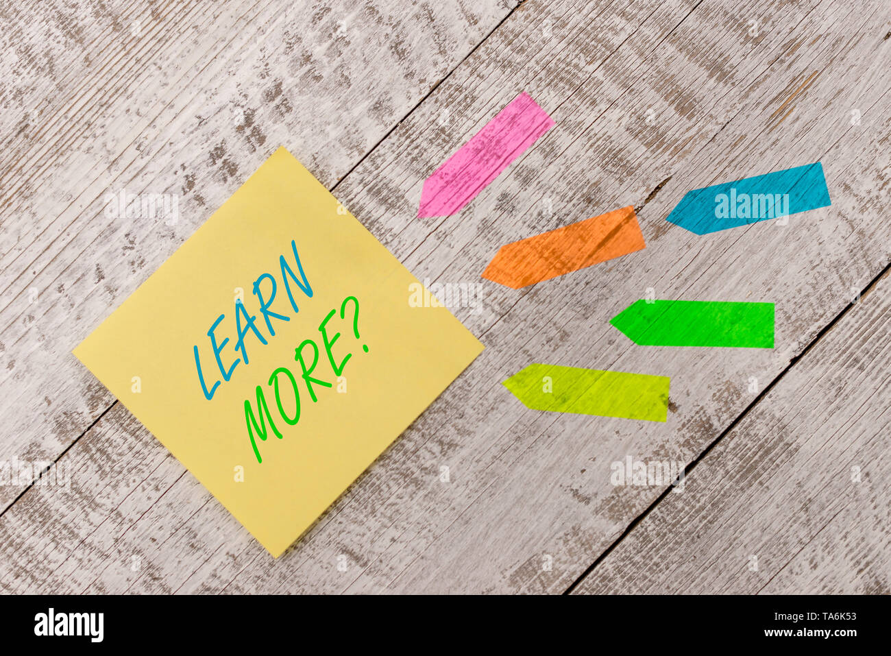 Word writing text Learn More question. Business photo showcasing gain knowledge or skill studying practicing Plain note paper and line arrow stickers  - Stock Image