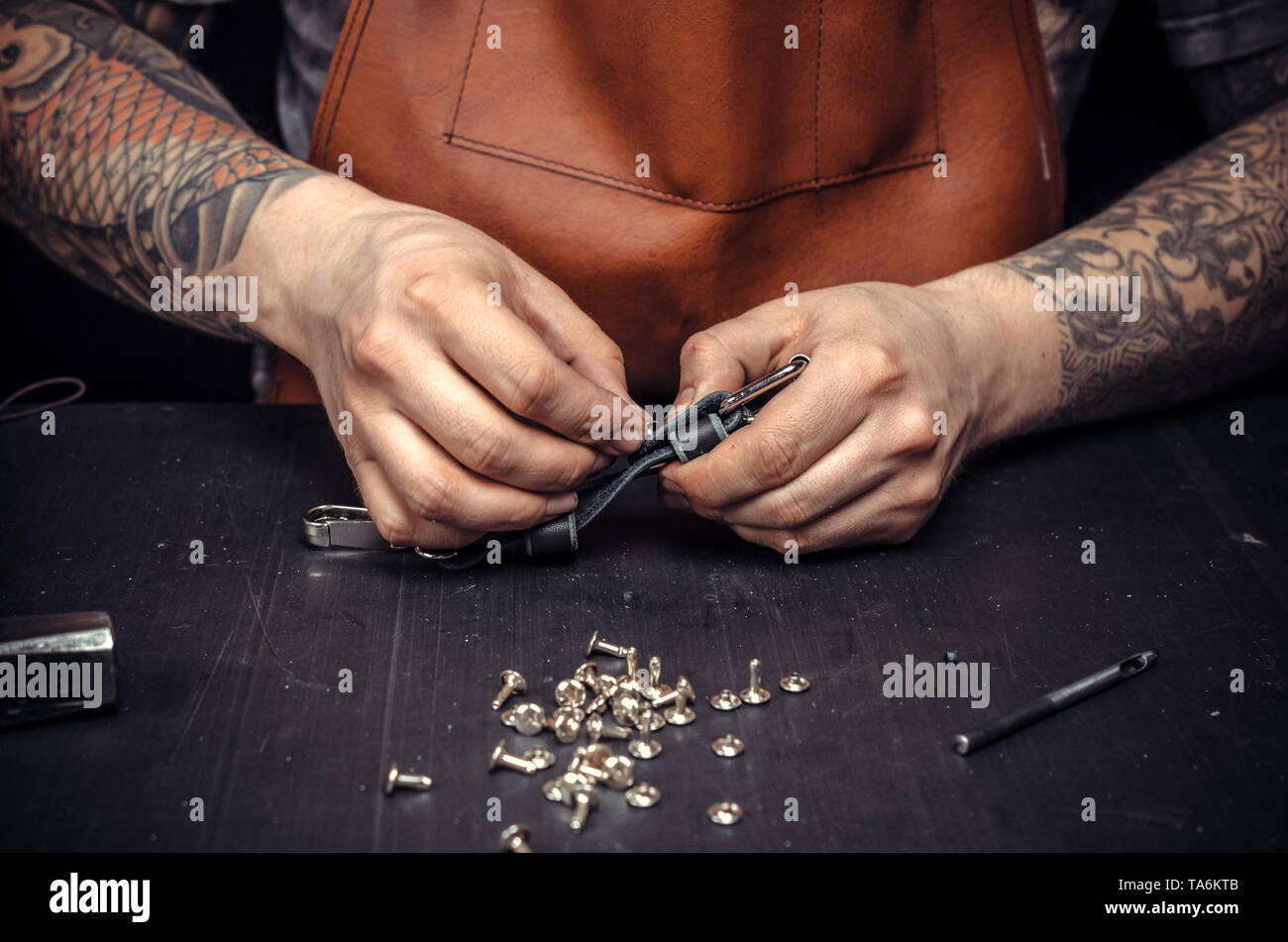 Leather workman creates quality product of leather at his place of work - Stock Image