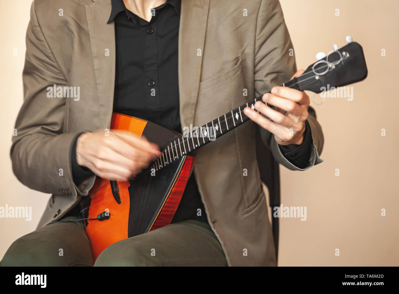 Man playing balalaika, closeup photo with soft selective focus and motion blur - Stock Image