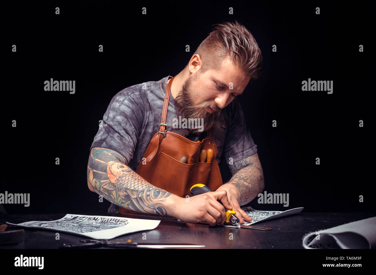 Leather Craftsman processing a leather workpiece in his tanner shop - Stock Image