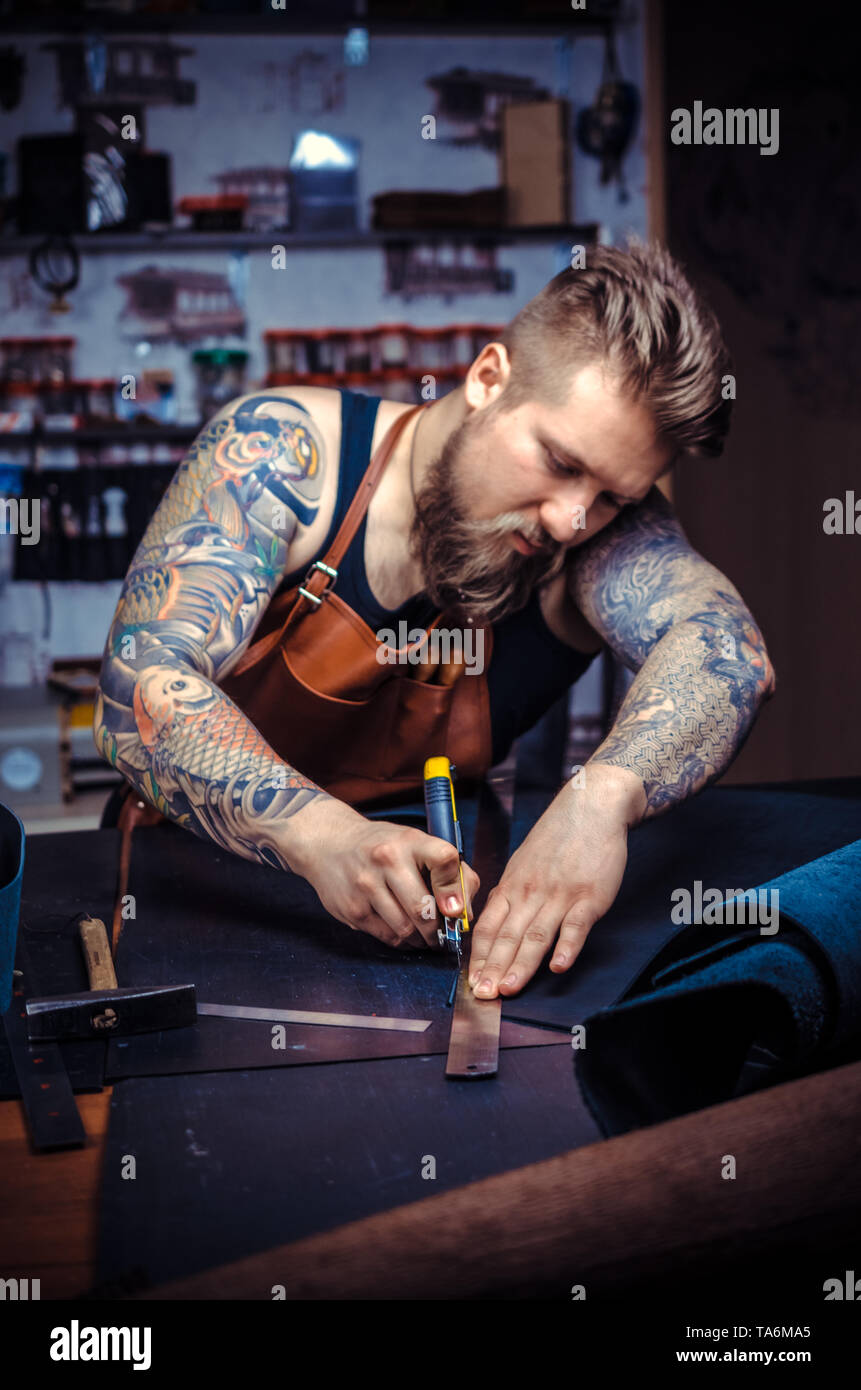 Currier of leather working on a new leather product in the tanner shop - Stock Image