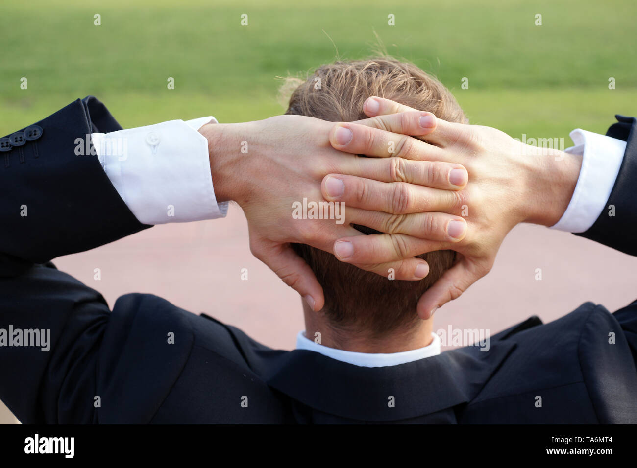 Young Businessman Relaxing in a Park while his Lunch Brake having his Hands Behind his Head - Stock Image