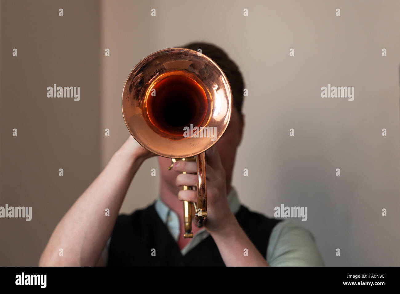 Trumpeter with trumpet in hands. It is a brass instrument commonly used in classical and jazz ensembles - Stock Image