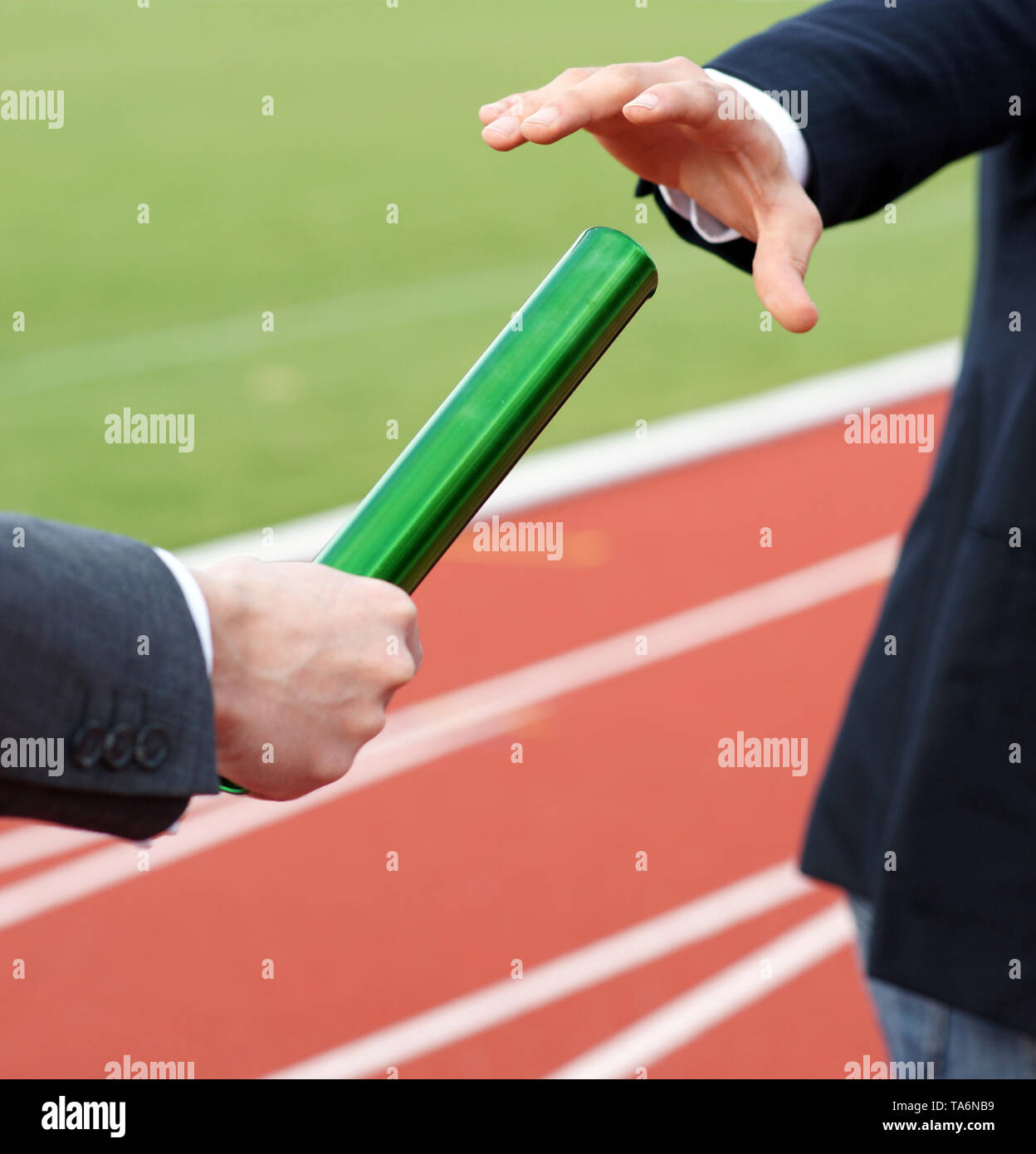 Businessman passing baton in relay race - Concept Teamwork Succession - Stock Image