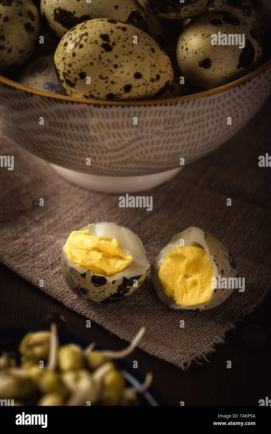 Vertical photo of single boiled quail egg broken in the middle. Other quail eggs are in bowl in background. eggs are placed on wooden board with mung  - Stock Image