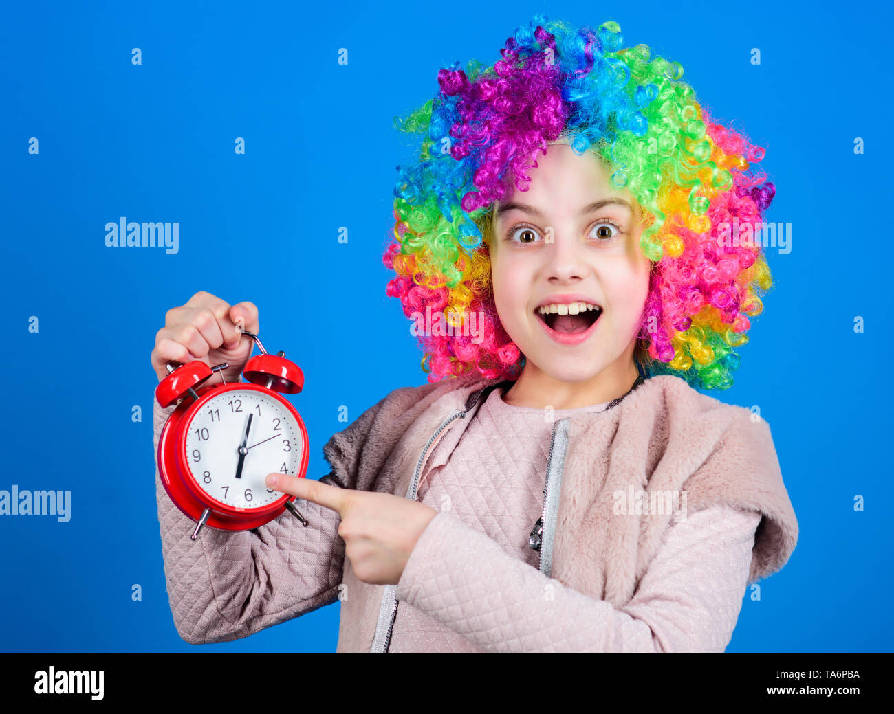 Focusing on accuracy. Happy small child pointing at alarm clock. Little girl smiling with clock. Accuracy and neatness. Perfect time accuracy. Accuracy concept. - Stock Image