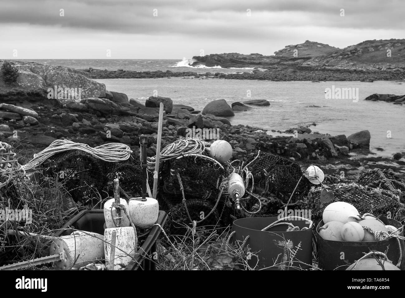 Lobster pots and other fishing gear, Porth Hellick, St. Mary's, Isles of Scilly, UK: black and white version - Stock Image