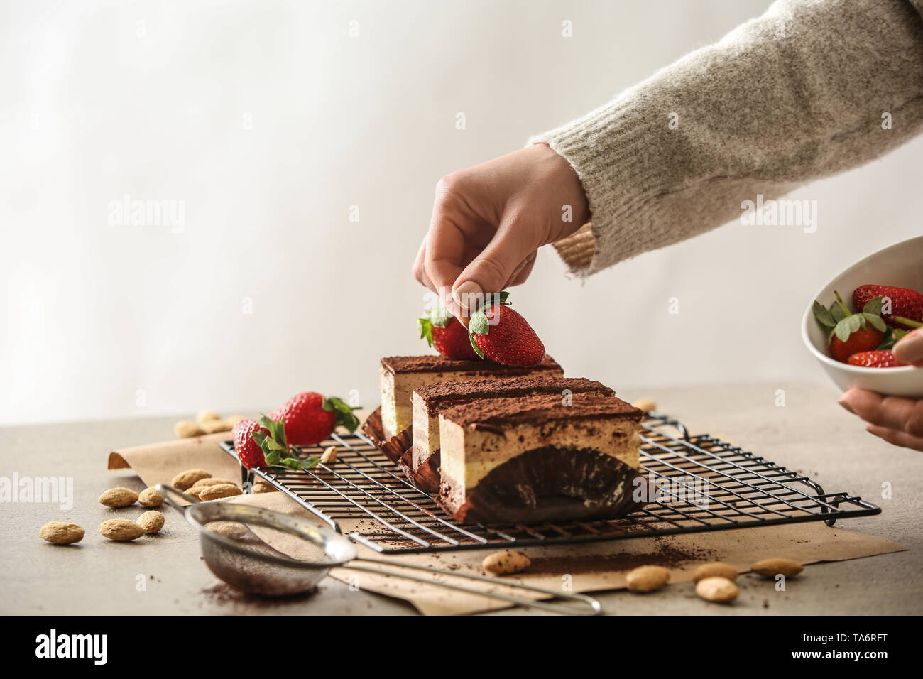 Female confectioner decorating tasty cakes at table - Stock Image
