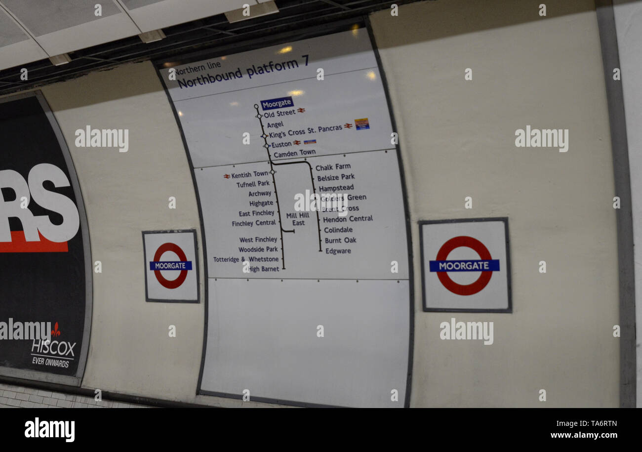 Metro stop in London, United Kingdom, June 14 2018. Among the informational signs the unmistakable red circular logo indicates the name of the station Stock Photo