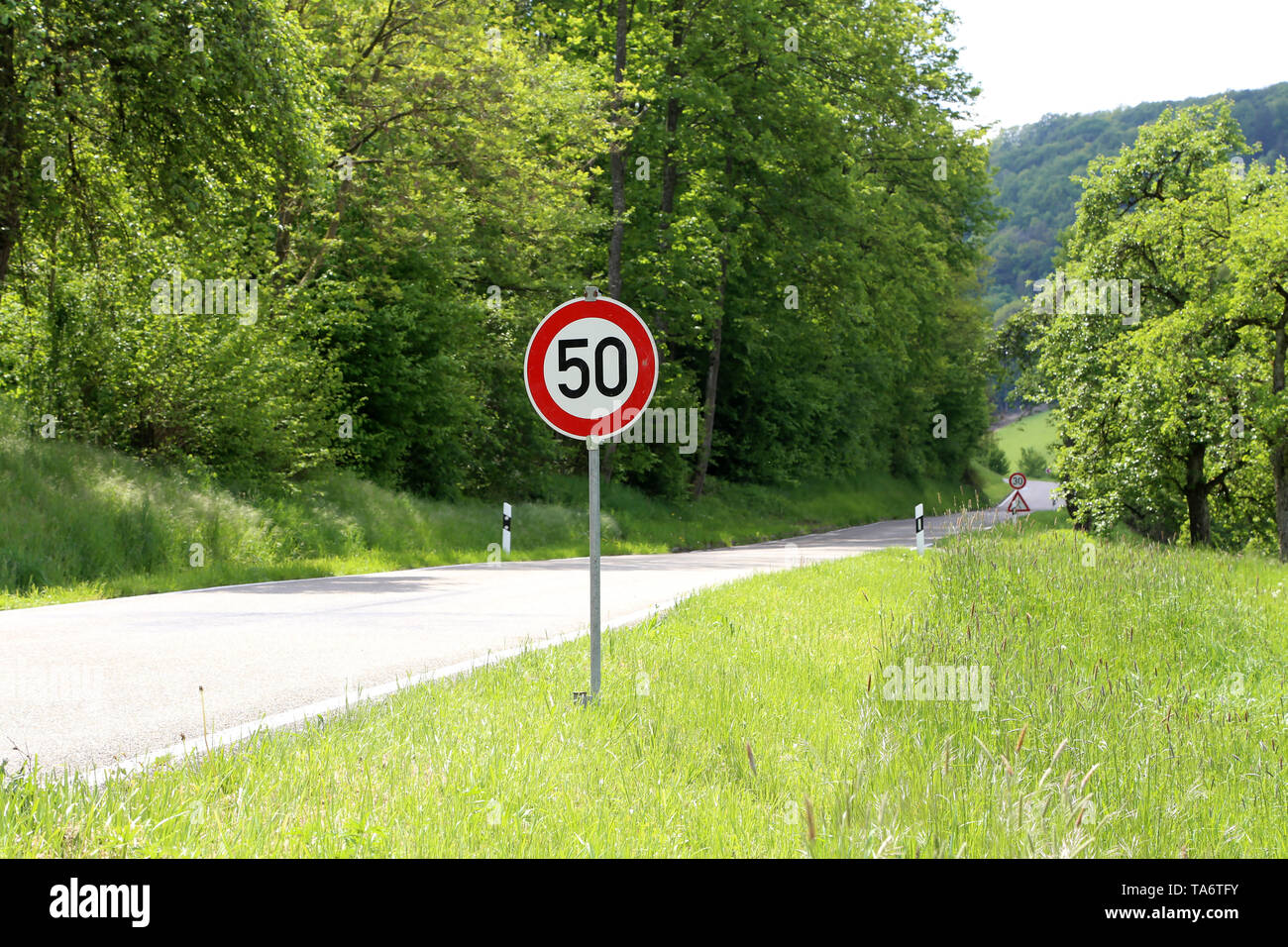 Various road signs on the road warn of danger. - Stock Image