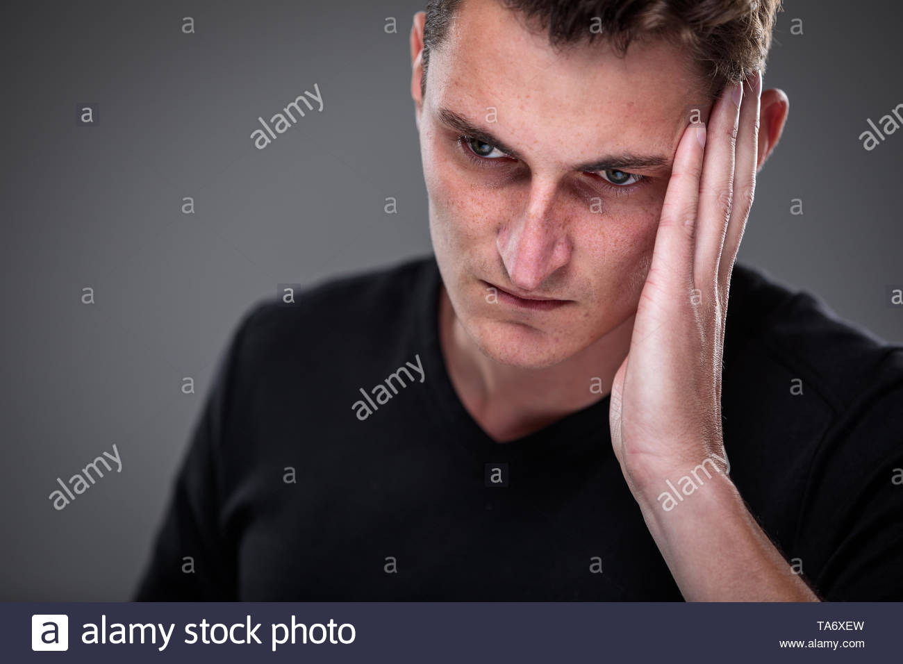Fear/anxiety/regret/uncertainty in a young man - effects of a difficult life situation - vivid emotions concept - Stock Image