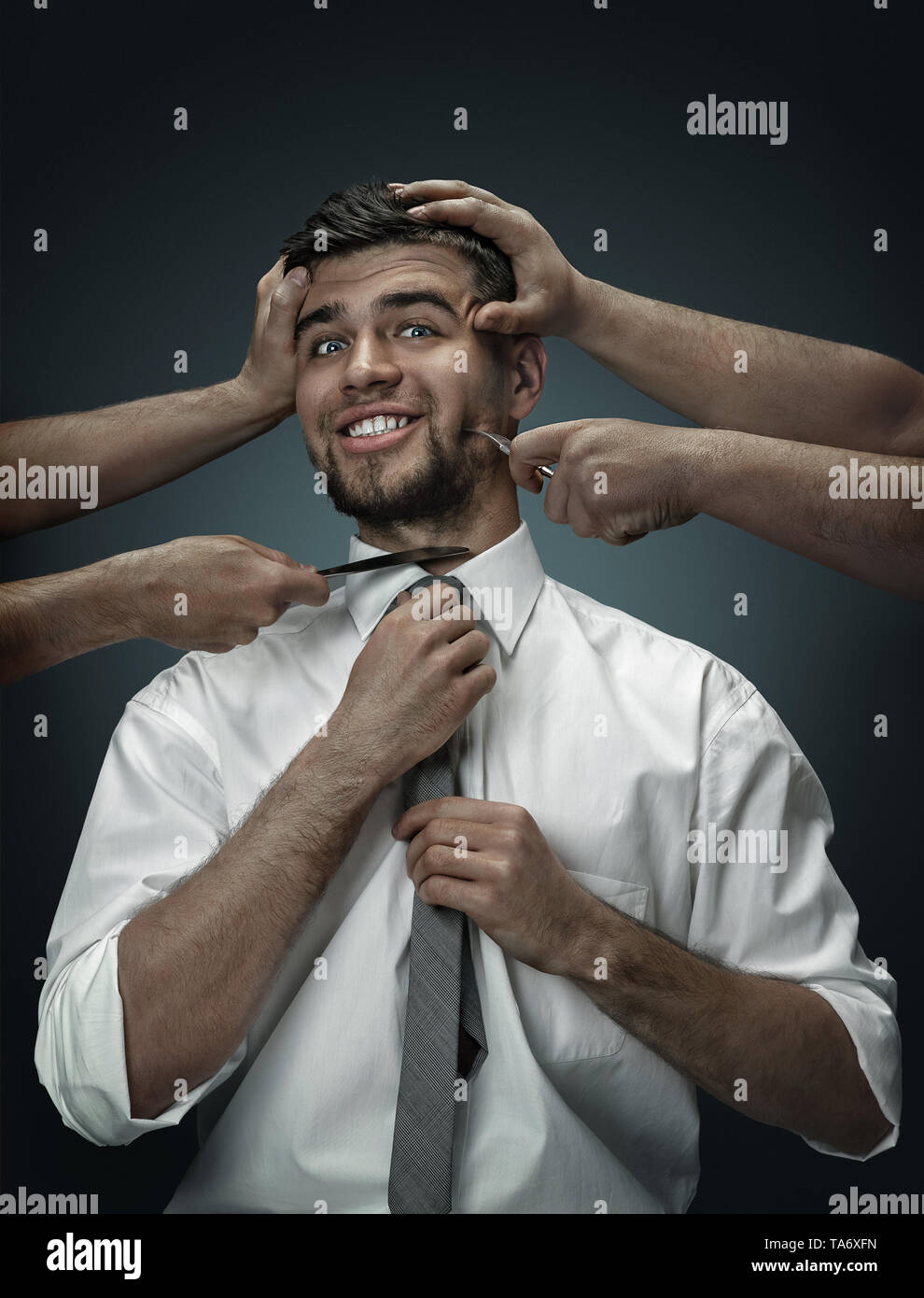 A male model surrounded by hands like his own thoughts on dark background. A young man doubts, is under the pressure of life situations. Concept of me - Stock Image