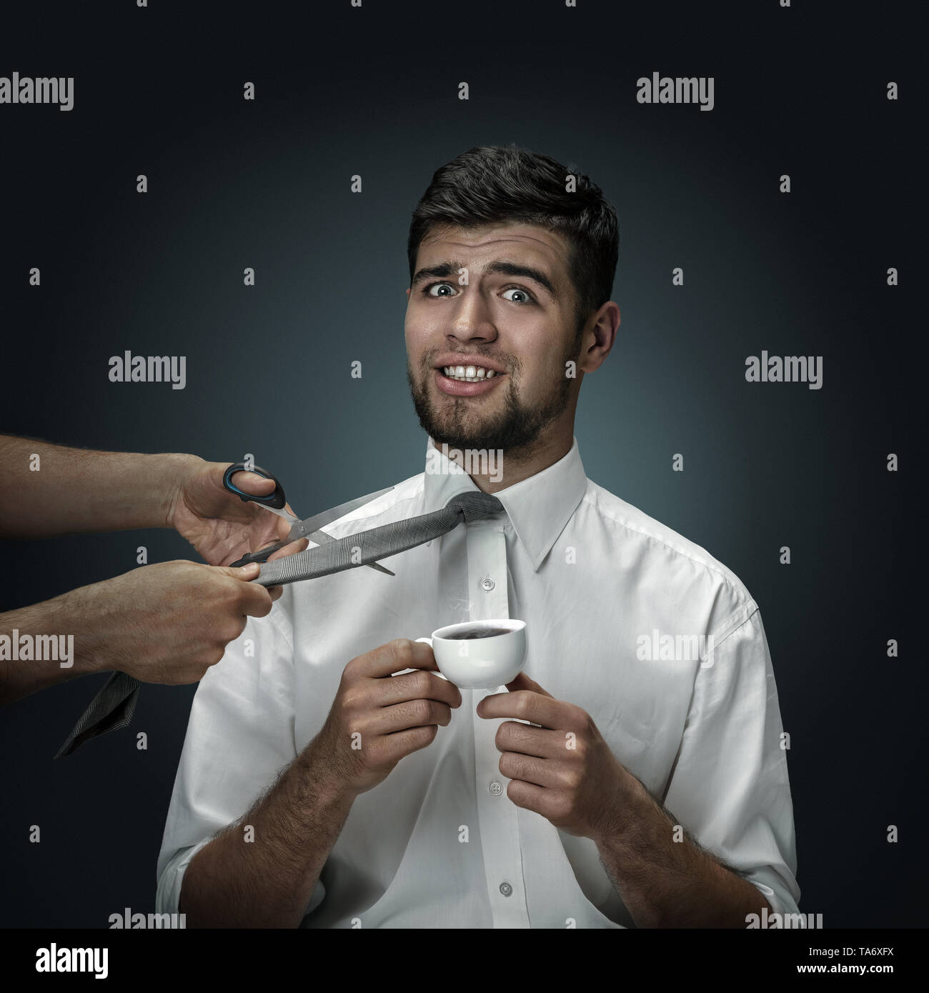 A male model with a cup of coffee on dark background. Hands behind the scene. A young man has no control in situation, his boss is firing him. Concept - Stock Image