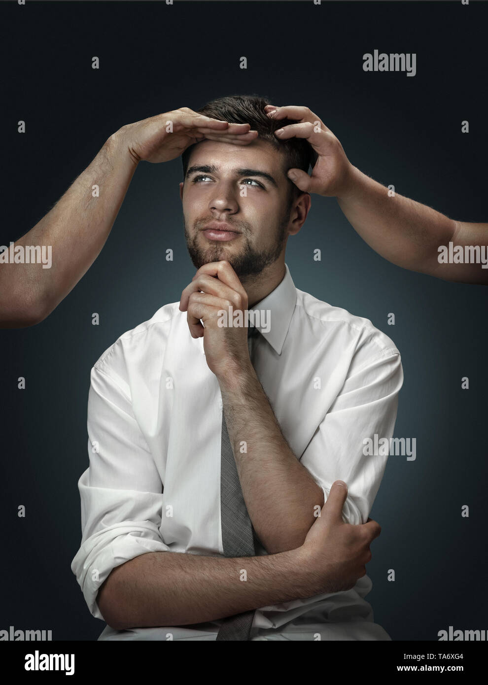 A male model surrounded by hands like his own thoughts on dark background. A young man doubts, can't choose the right decision and dreams. Concept of  - Stock Image