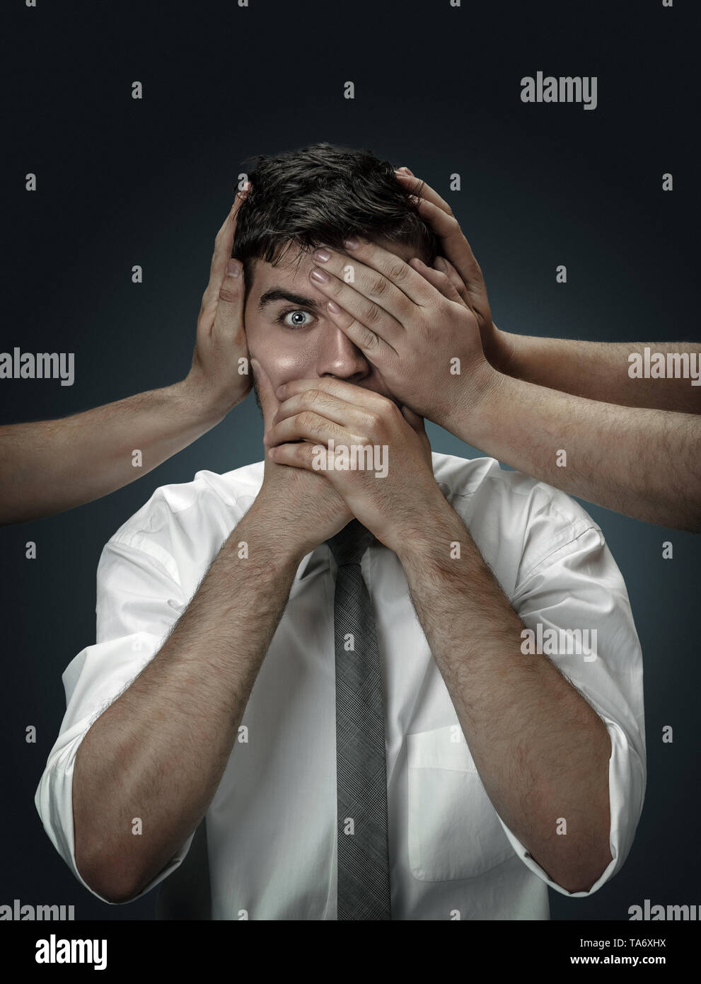 A male model surrounded by hands like his own thoughts on dark background. A young man doubts, can't choose the right decision and decide. Concept of  - Stock Image