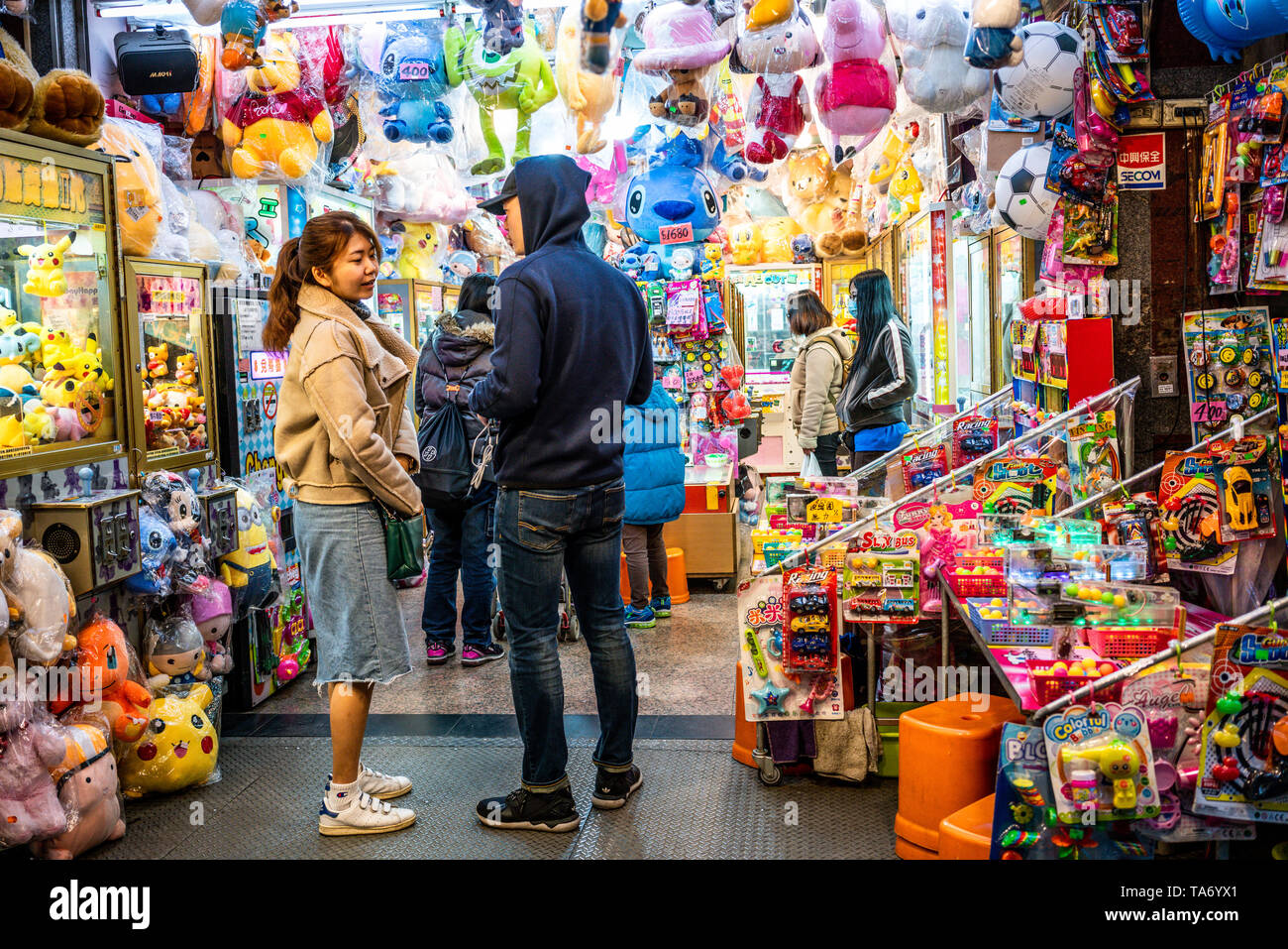 13 February 2018, Taipei Taiwan : Young Asian adult couple on the porch of a colorful toys and games shop in Taipei Taiwan - Stock Image
