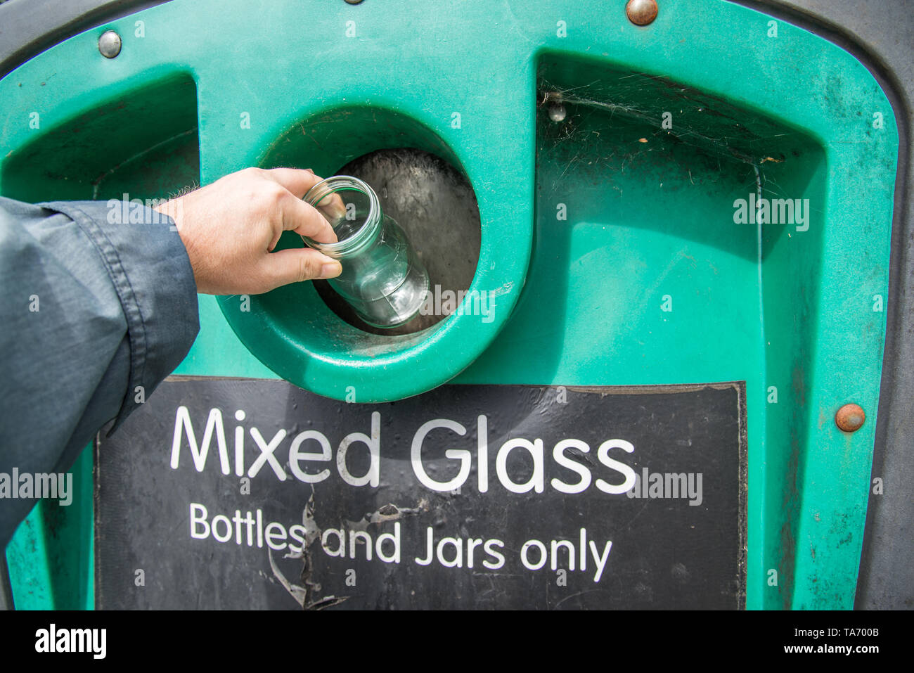Putting glass bottles and jars into collection bin at local recycling center,Hampshire,UK.bottle bank. - Stock Image