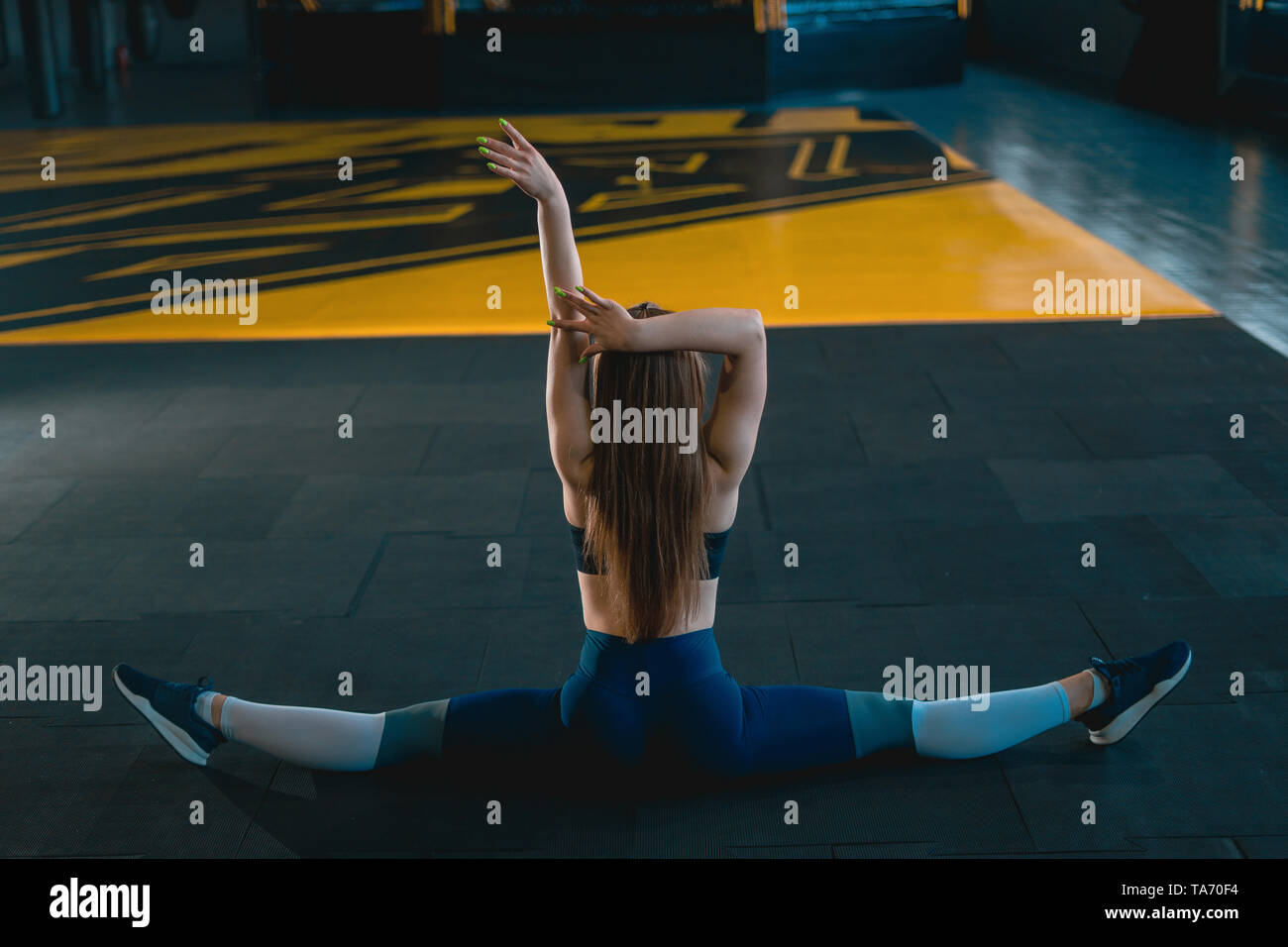 Stretching gymnast girl doing vertical split, twine  Side view of