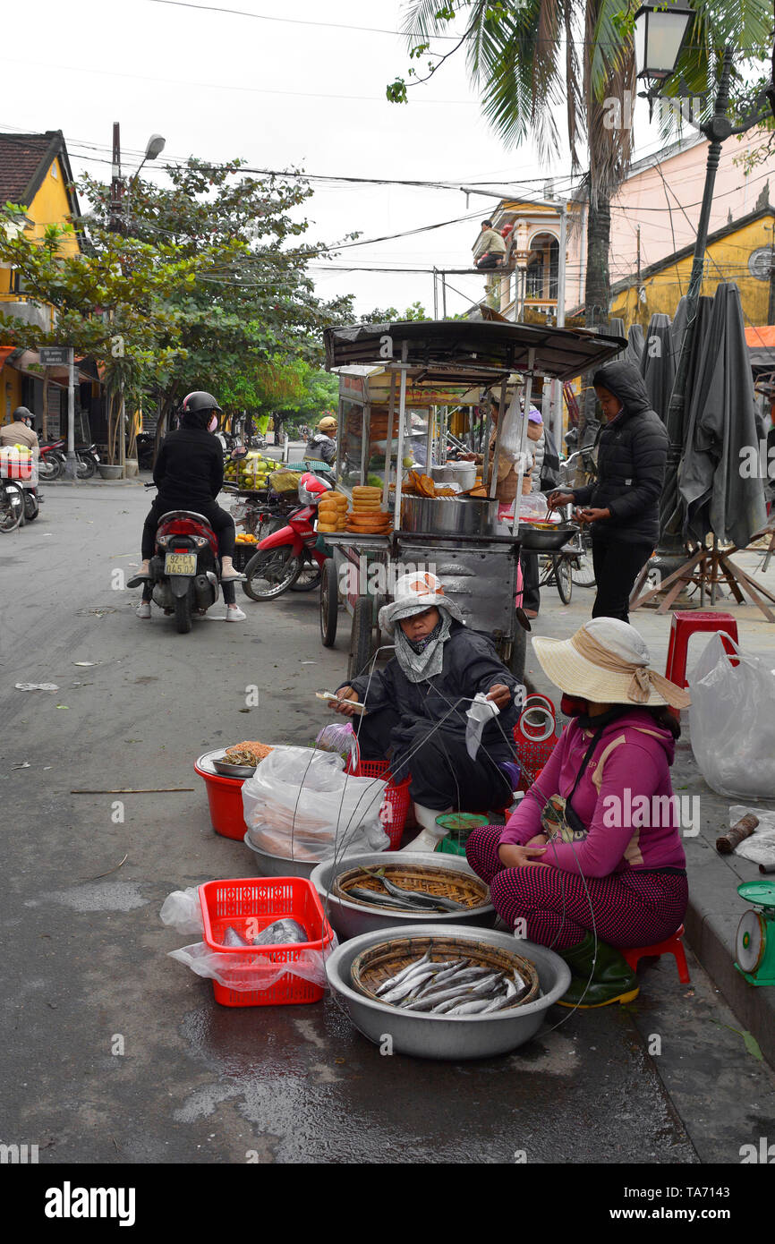 Hoi An, Vietnam - December 20th 2017. Street vendors selling fish wait for customers by the outdoor market in the historic UNESCO listed Vietnamese to - Stock Image