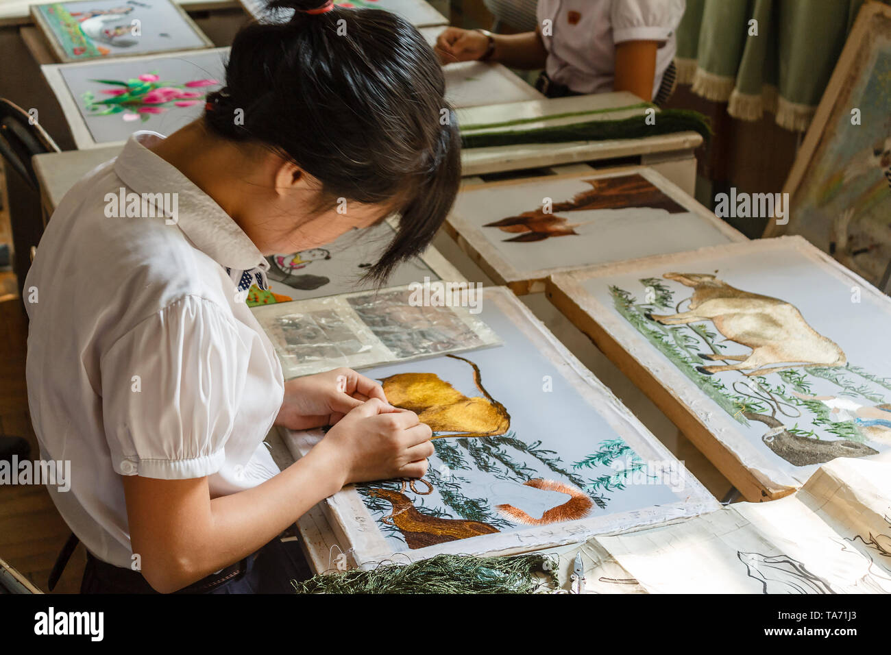 Pyongyang, North Korea - July 29, 2014: Korean girl embroiders a picture in the Pyongyang Palace of schoolchildren. Extracurricular educational instit - Stock Image