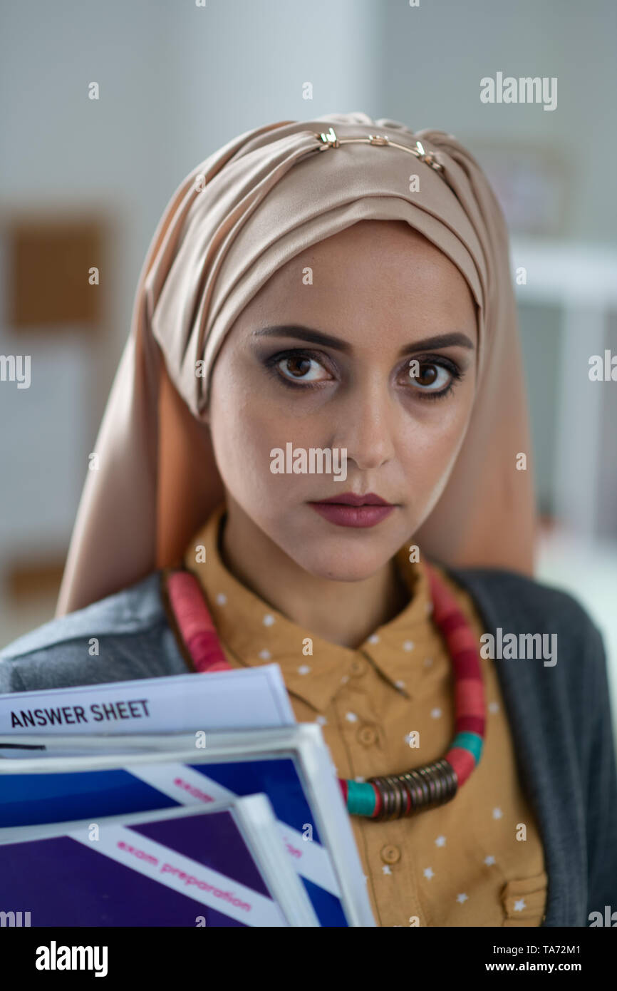 Dark-eyed Muslim teacher holding books standing in school Stock Photo
