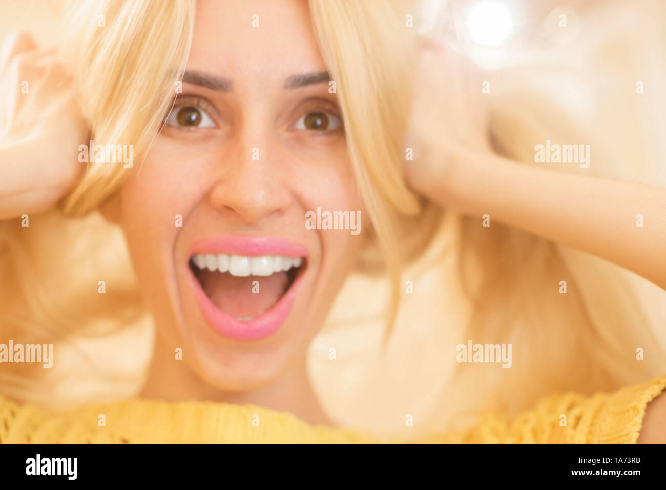 Portrait of lovely smiling young girl doing ponytails with long hair and laughing playfully - Stock Image