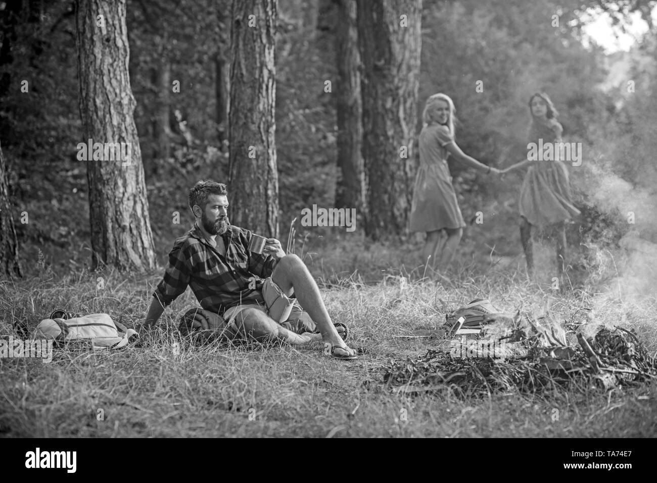 Bearded man drink tea or coffee at bonfire with women on blurred background. Bearded man sit at campfire - Stock Image
