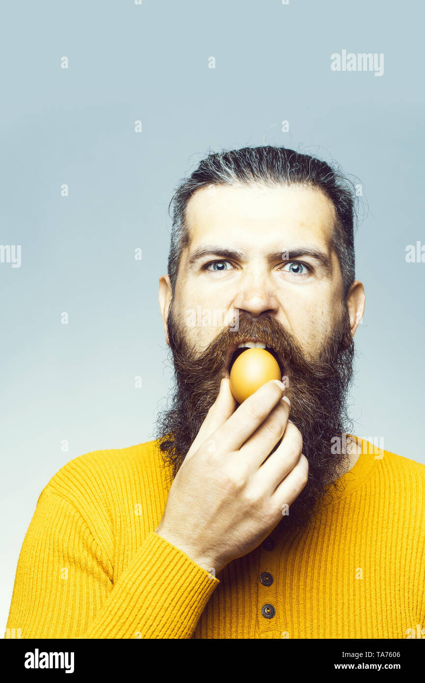 serious bearded man with egg - Stock Image