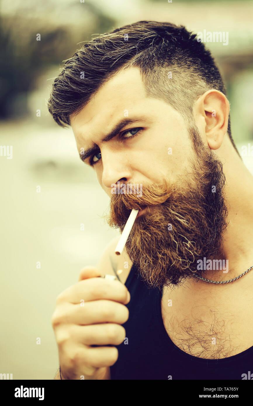 Bearded man lights cigarette - Stock Image