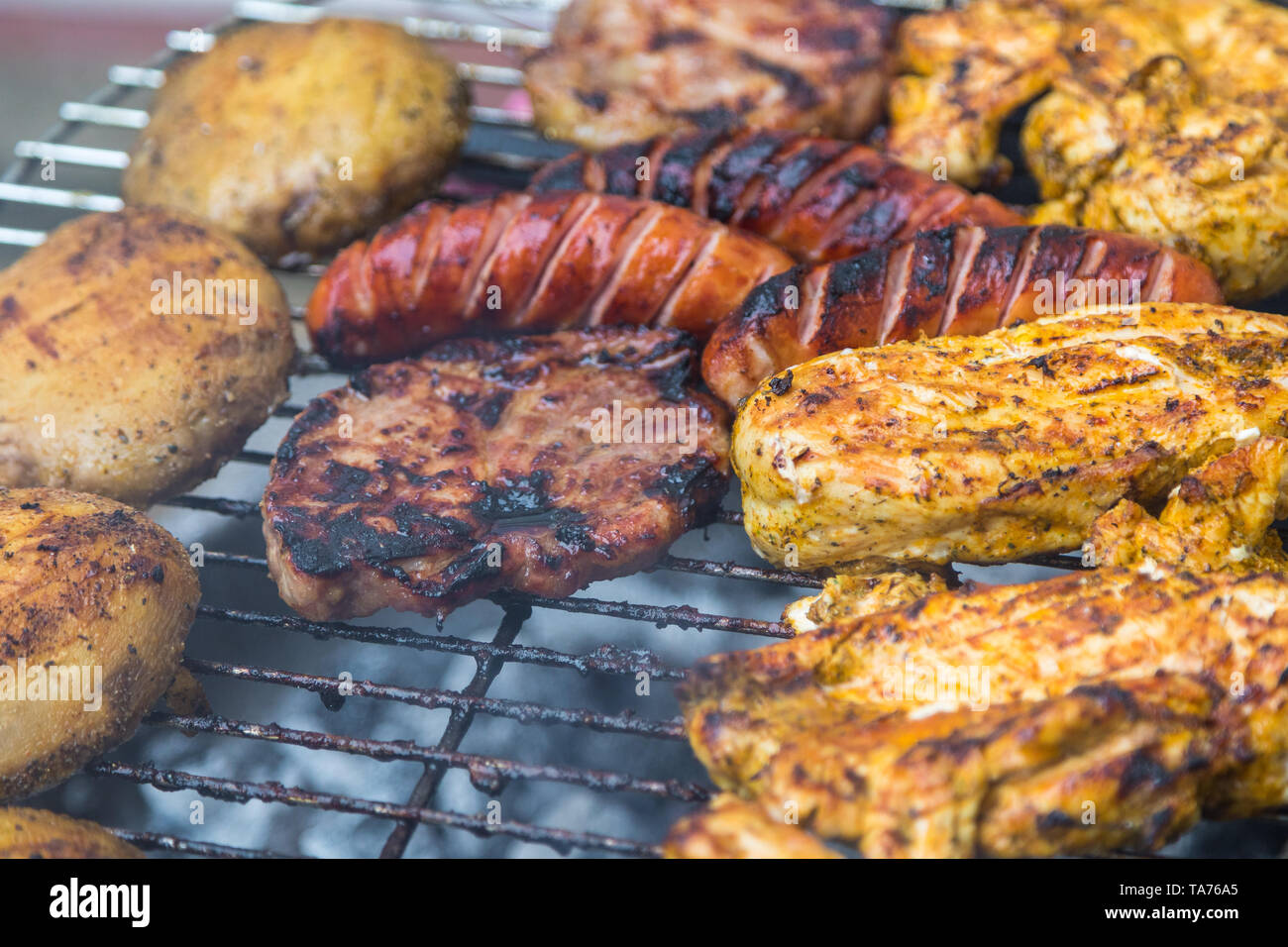 Assorted delicious grilled meat with potatoes over the coals on a barbecue. - Stock Image