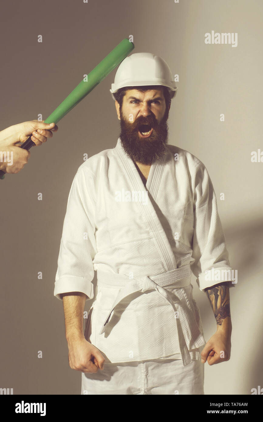 bearded karate man, long beard, brutal caucasian hipster with moustache in white kimono with black belt, builder helmet holds green baseball bat with  - Stock Image