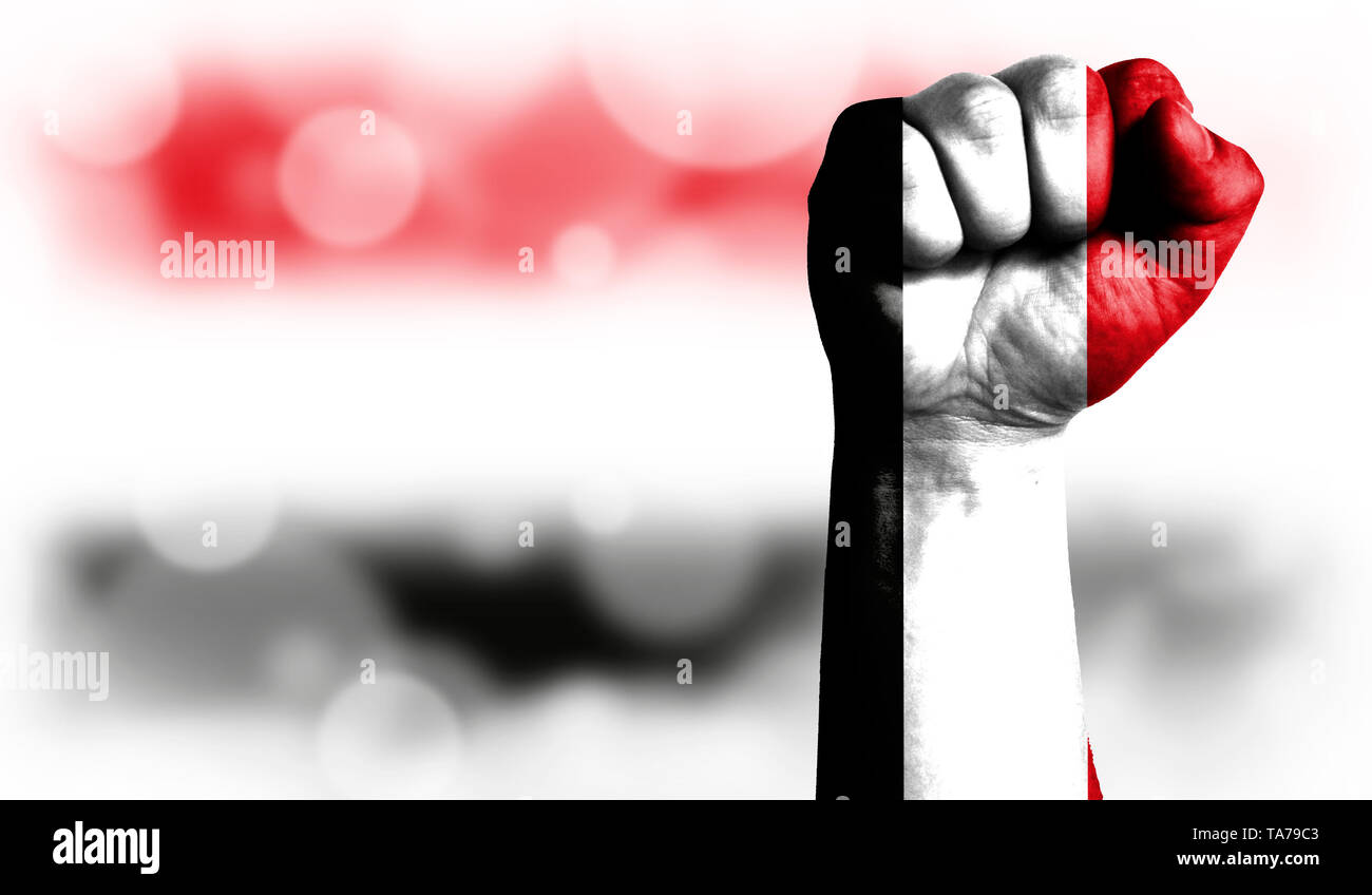 Flag of Yemen painted on male fist, strength,power,concept of conflict. On a blurred background with a good place for your text. - Stock Image
