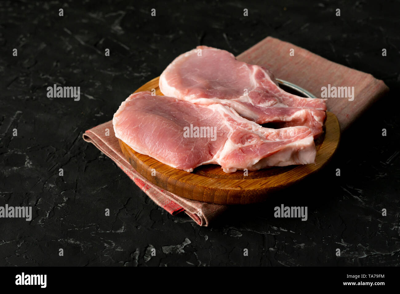 top view of raw meat uncooked slices, cut pork on a wooden board isolated - Stock Image