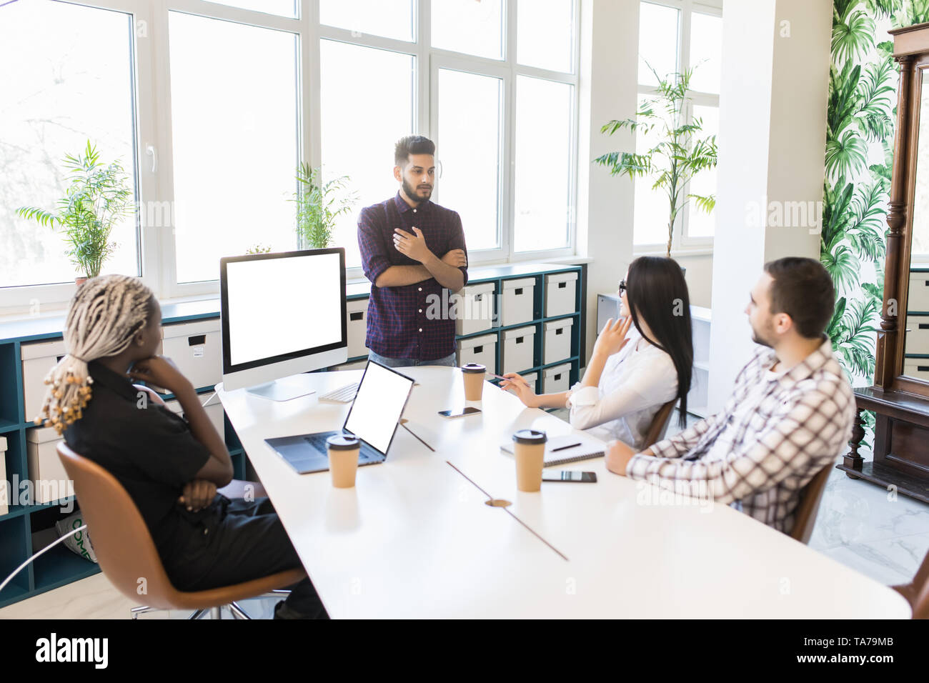 Brainstorming in a boardroom of creative office . Young creative people sitting at the table and discussing new projects. - Stock Image