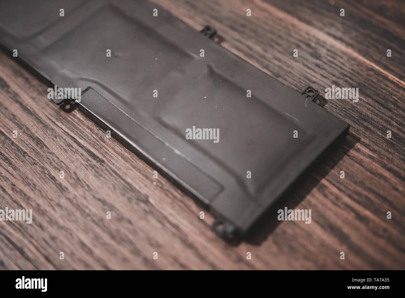 Swollen Lithium Polymer (Li-Po) laptop battery on a wooden table. Known issue for modern laptop and gadget - Stock Image